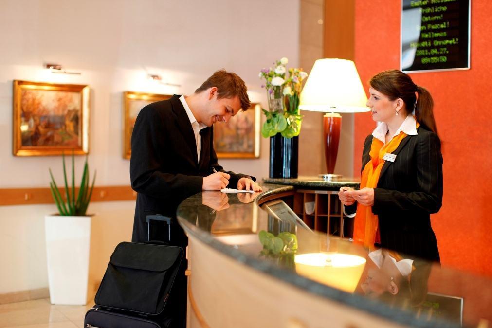 Nhân viên lễ tân lưu thông tin của khách
